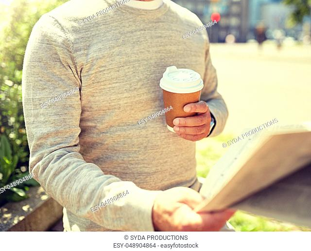 senior man with coffee reading newspaper outdoors
