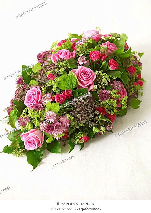 Flower arrangement including spray roses, astrantia, alchemilla, salal, viburnum, close-up