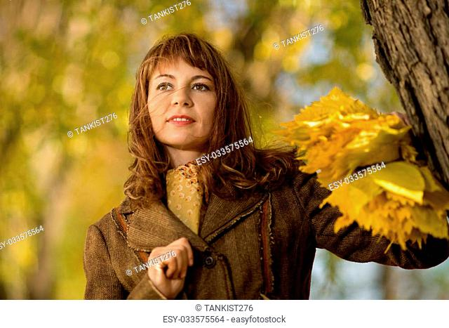 mature beautiful woman, horizontal portrait, outdoor in park, autumnal day