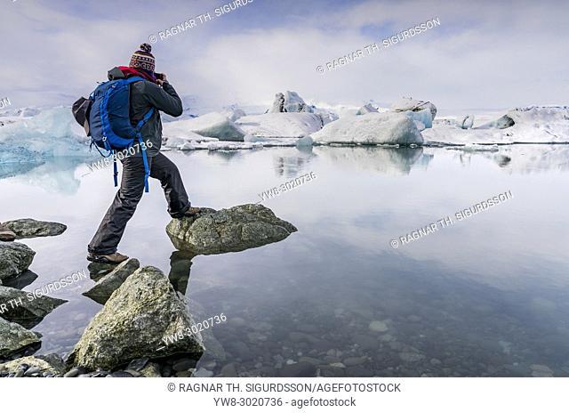 Tourist taking pictures, Jokulsarlon Glacial Lagoon, Iceland