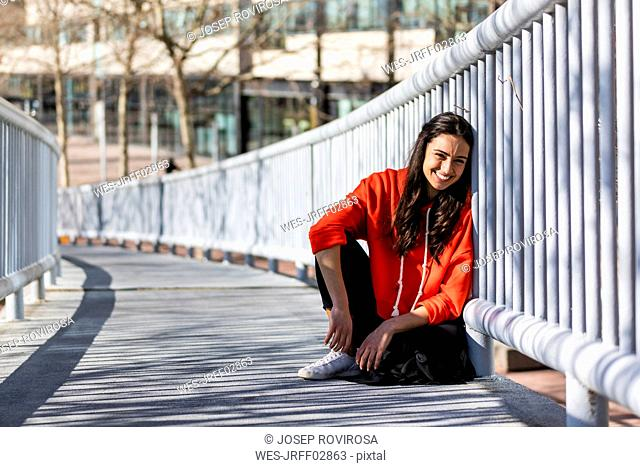 Young contemporary dancer sitting on a footbridge, resting
