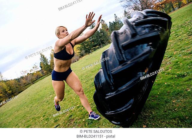 Caucasian woman pushing heavy tire up hill
