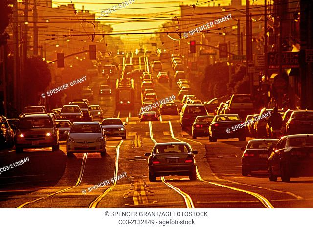Setting sun shines on afternoon traffic on Taraval Street in San Francisco. Note trolley tracks