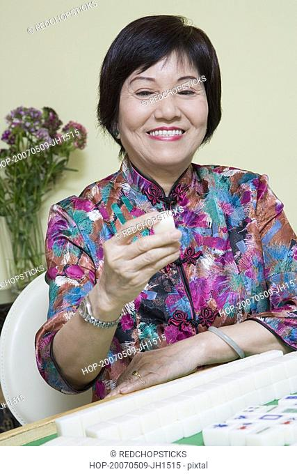Senior woman playing mahjong and smiling