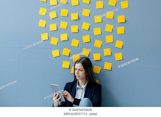 Young businesswoman usig digital tabet, sitting under data cloud