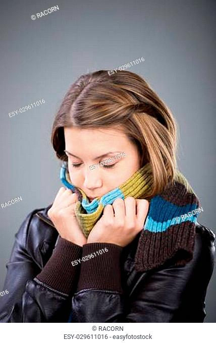 Woman freezing with scarf and jacket isolated on
