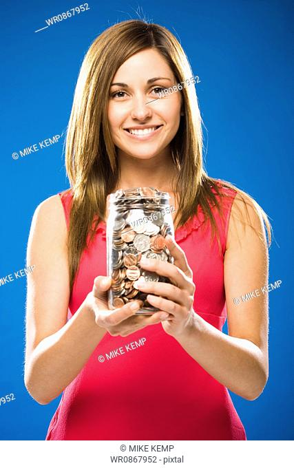 Woman holding jar filled with coins smiling