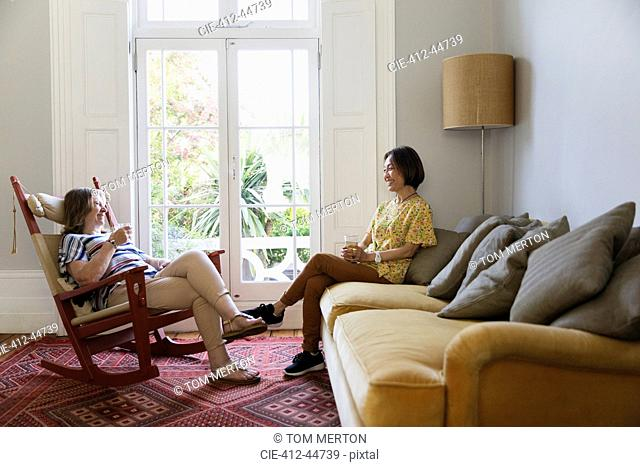 Senior women friends talking in living room