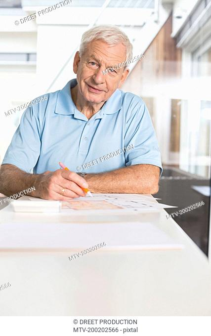 Senior man writing on document at home