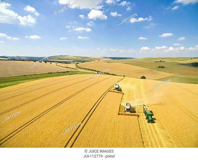 Scenic aerial landscape view of combine harvesters and tractor in sunny barley field