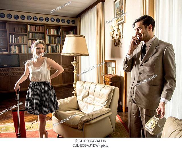 Young vintage couple in sitting room with vintage telephone and vacuum cleaner