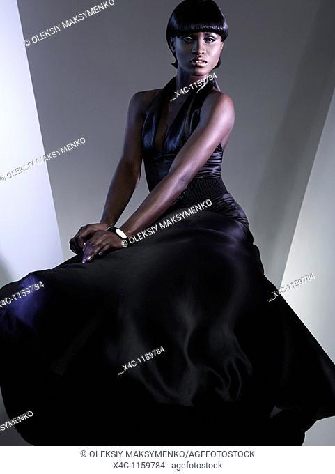 Beautiful young woman wearing long black dress  High fashion photo