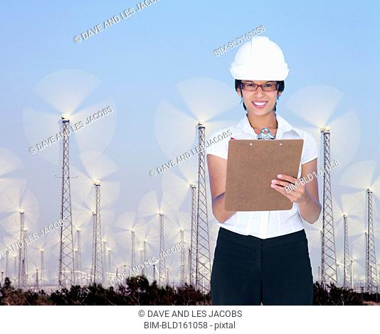 Mixed race businesswoman holding clipboard at wind farm