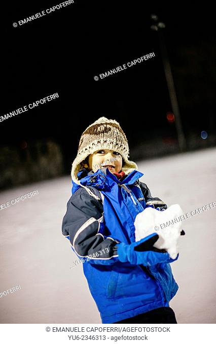 Child plays with snow in the evening lit by streetlights