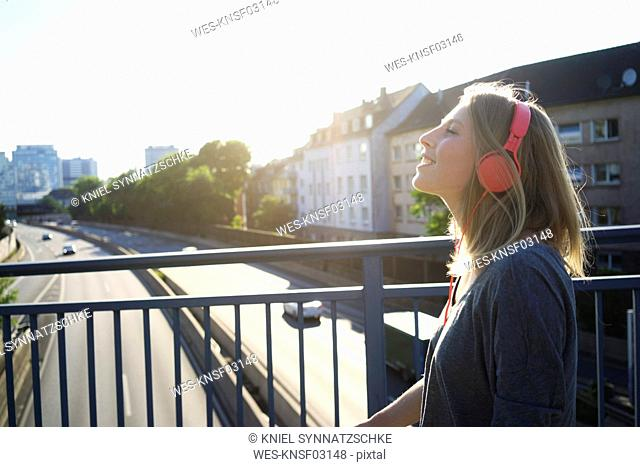 Smiling young woman on a bridge listening music with headphones