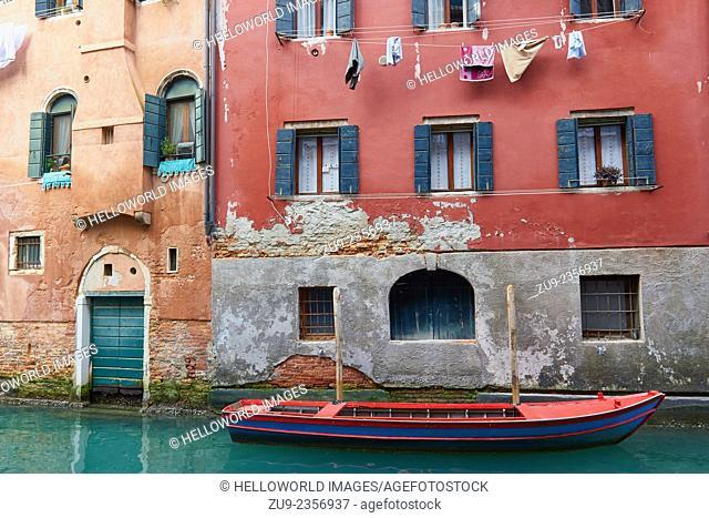 Boat moored outside canalside houses, Venice, Veneto, Italy, Europe