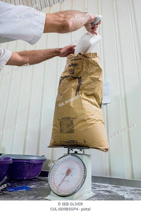Baker weighing flour in bakery