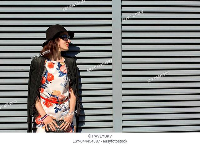 Stylish brunette girl wearing stylish dress and sunglasses, posing near the shutters at the street. Space for text