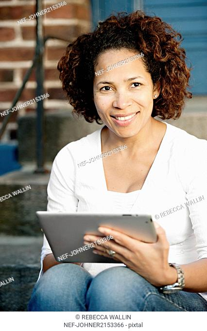 Woman holding digital tablet, looking at camera