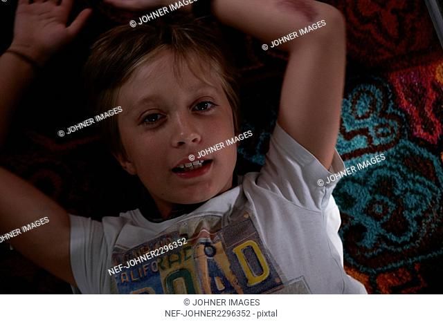 Portrait of smiling boy lying on carpet