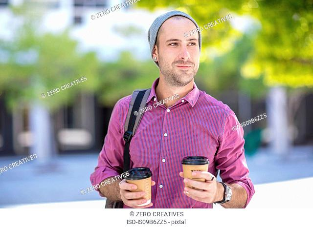 Young man outdoors, holding two takeaway coffee cups