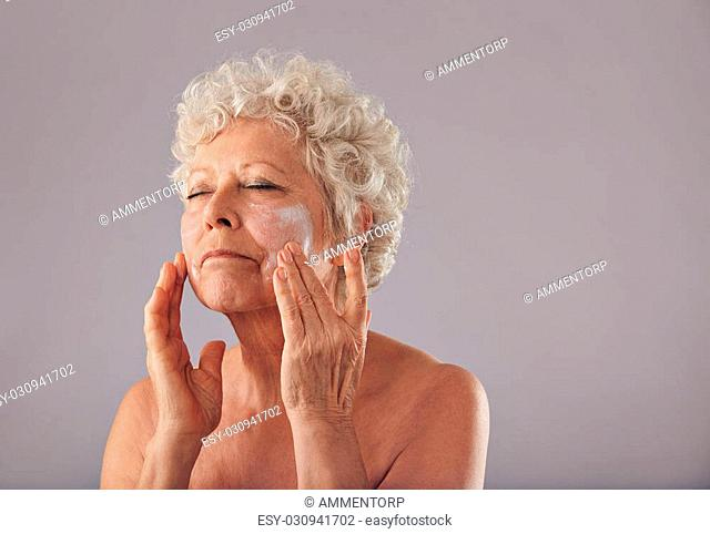 Portrait of senior woman applying lotion on her face against grey background. Mature caucasian woman applying anti-wrinkle face cream