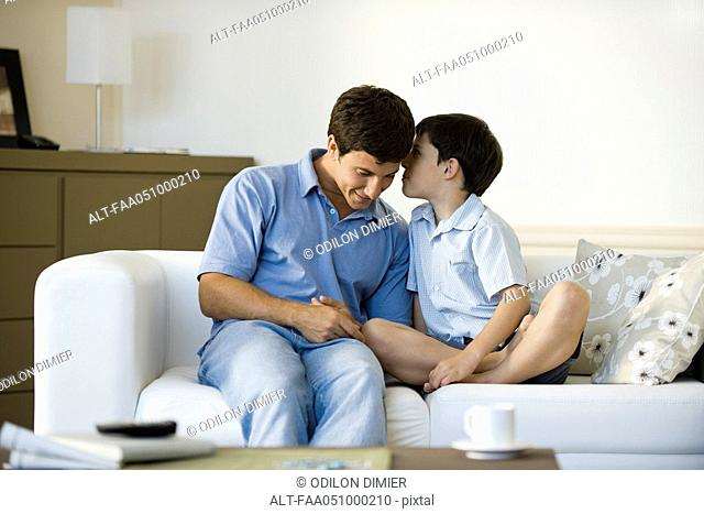 Young son whispering secret to father