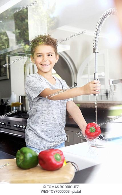 Boy washing vegetables in kitchen