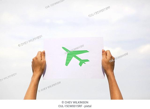 Arms holding paper green plane