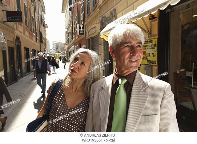 Senior couple strolling through town, Italy