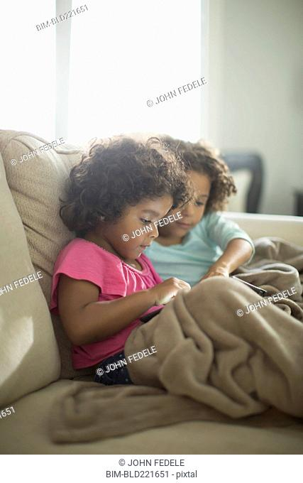 Sisters using digital tablet on sofa