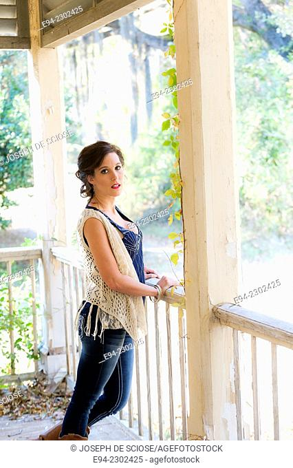 36 year old brunette woman outdoors standing on a porch of an old house looking over her shoulder directly at the camera