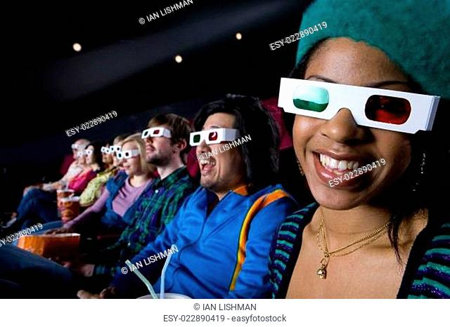 Audience in cinema wearing 3D glasses, smiling, portrait