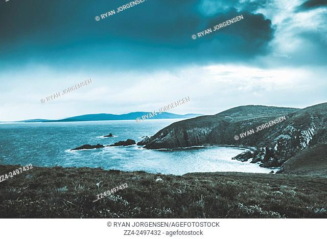 Dark tense and dramatic landscape photo on a stormfront gathering over the rocky cliffs of the most Southern part of Bruny Island, Tasmania, Australia