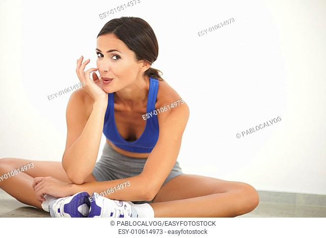 Sporty pretty woman in sport clothing sitting for relaxation and smiling