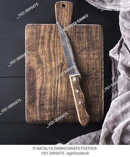 very old rectangular cutting board with handle and kitchen knife, top view