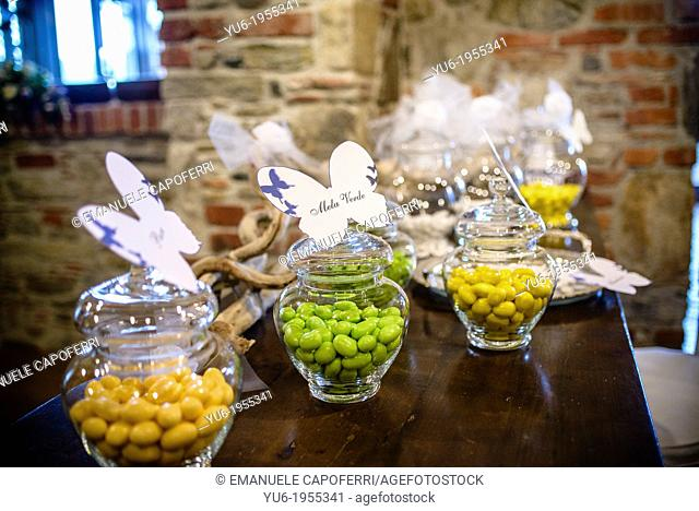 Glass vases with colorful sugared almonds at a wedding