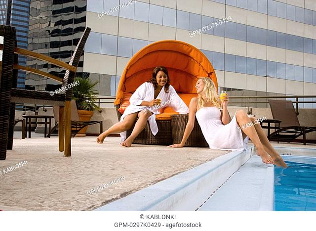 Young women relaxing near swimming pool on rooftop terrace