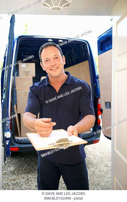 Caucasian delivery man getting signature for package