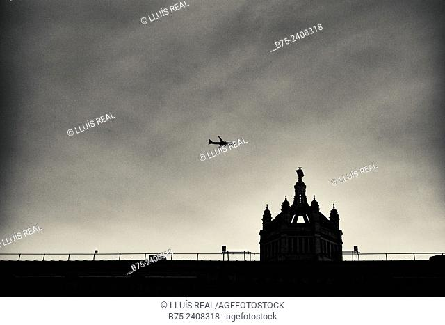View of a dome of the Victoria and Albert Museum with an airplane flying in the sky. South Kensington, London, England, UK