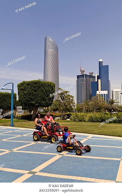 People with pedal cars on Abu Dhabi Corniche; Abu Dhabi, United Arab Emirates