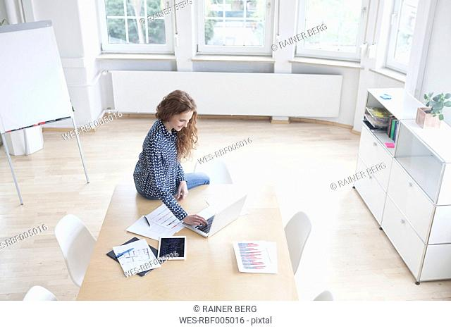 Woman using laptop in boardroom