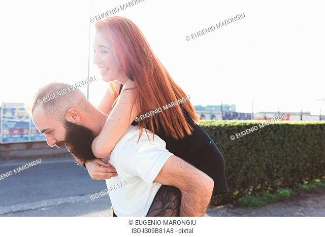 Man giving red haired woman piggyback