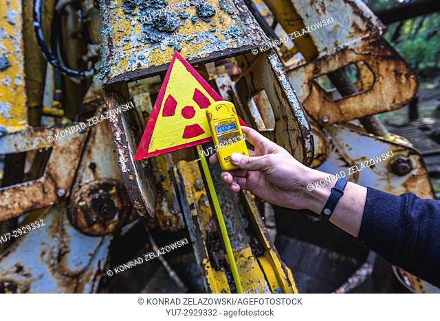 Tourist examine irradiated scrap bucket in Pripyat city of Chernobyl Nuclear Power Plant Zone of Alienation around nuclear reactor disaster, Ukraine
