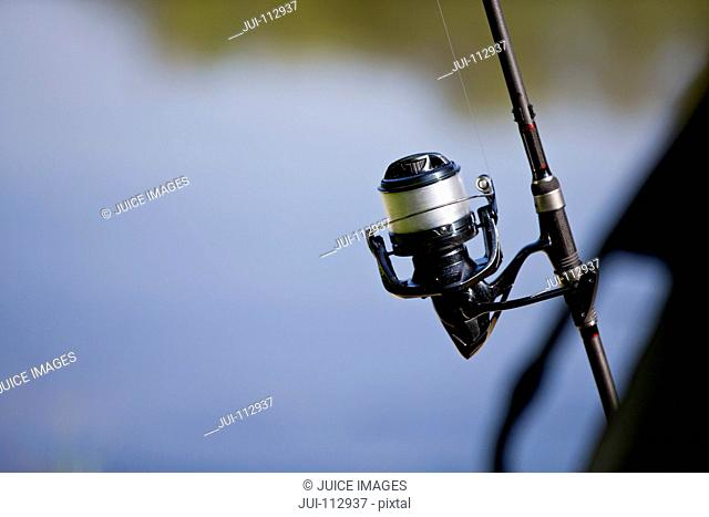 Close up of fishing rod and line against defocused lake