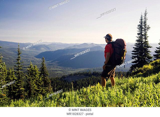 Man backpacking in the mountains, walking on a ridge overlooking a valley