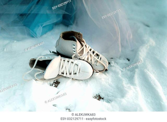 White leather shoes with skates lying in the snow