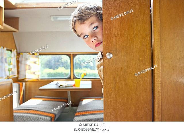 Boy peeking round door in caravan