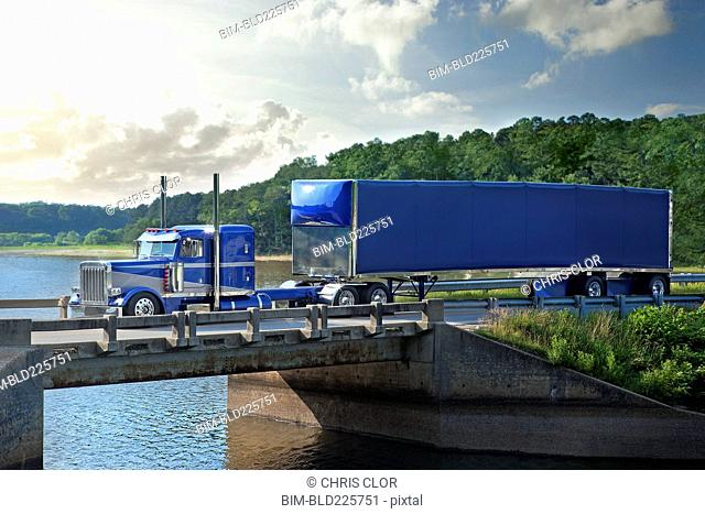 Semi-truck driving on bridge over river
