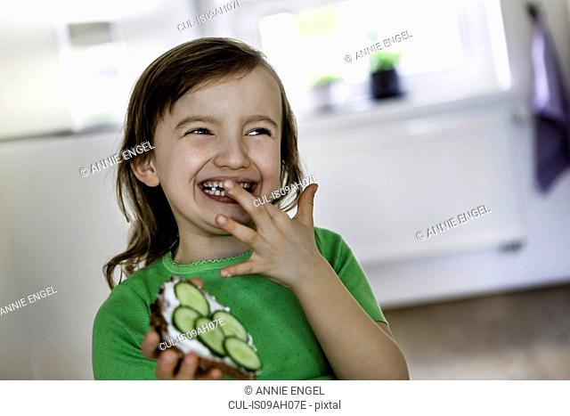 Smiling girl with an open sandwich